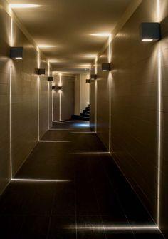 A iluminação com arandelas altas fez toda a diferença para esse corredor comprido e todo fechado. Interessante como a luz vai do teto até o chão formando linhas e como se intercalam, diminuindo assim a sensação de profundidade.
