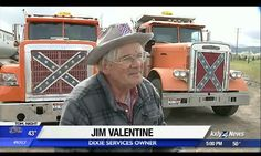 Screenshot of Dixie Services owner Jim Valentine wearing a hat showing the confederate flag and before two giant trucks with the confederate flag on front.