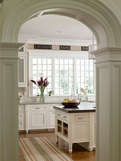 arch, white columns and moulding, window above the sink, hand painted signs