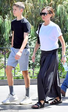 Family matters: David and Victoria Beckham (pictured) took their children Romeo (L), Cruz and Harper (R) for a fun day out at Disneyland on Saturday - while son Brooklyn partied at the Coachella Festival in Palm Springs