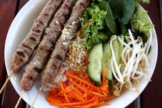 VIETNAMESE -- Bún nem nướng – Vermicelli noodles with grilled pork skewers. Nem nướng served with cold vermicelli noodles, lots of fresh herbs, lettuce, bean sprout, cucumber, pickled carrots and fish sauce dipping sauce.