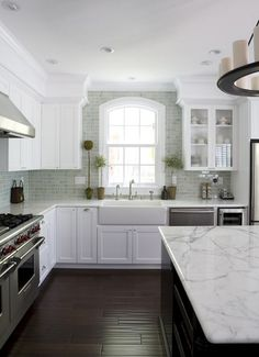 White farmhouse sink in white kitchen with seagreen backsplash and dark hand-scraped hardwood floors