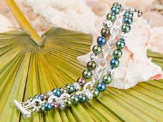 Warm up with a tropical treat when you wear this colourful multi-strand bracelet. The lovely peacock colour palette is inspired by the vibrant lifestyle on the Caribbean island that shares this designs' name.