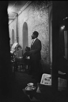 """THELONIOUS MONK TAKES FIVE AT THE BLUE ANGEL, 1963 Columbia staff photographer Don Hunstein caught Monk between numbers, standing near the jukebox at Manhattan's fabled Blue Angel. Interestingly, on February 28, 1964, Time Magazine featured Thelonious, """"The Loneliest Monk,"""" on its cover. Photo by Don Hunstein. Sony Collectibles. All rights reserved. jazz.com"""