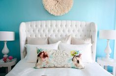 love the tufted headboard and the pretty blue walls.