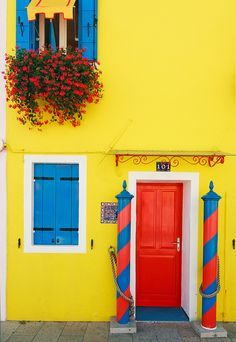 Italian Flair Bold colours frame a doorway of a typical home in Burano, a Venetian island known for its bright colours and lace work. The colours of the homes follow a strict tradition and permission is needed from the government who respond by indicating what colours are allowed. Love the yellow!