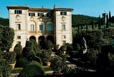The exterior of the home known as Villa Cetinale includes topiaries, lemon trees, and statues of the four seasons.