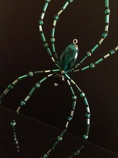 """Green, black and silver beaded spider. Approx. 6""""x .5""""x 3""""."""
