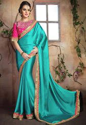 Faux satin chiffon saree in turquoise. This ensemble features zari and sequins work in geometric and ornamental motifs. It is enhanced with patch border work. As shown, a fuchsia art silk blouse in unstitched form is available. Do note: Slight variation in actual color vs. image is possible.