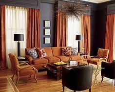 A palette of navy blue and rusts adds warmth to this north-facing living room. Along rust-color sofa the Tangerine, color of the year. grouping includes Bentwood chairs, tufted black vinyl chairs, and faux bamboo side tables.
