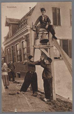De klokkenpaal voor het postkantoor op de Dijk. Drie jongens in dracht poseren: één is op de paal geklommen, twee anderen luiden de klok. 1910-1920 #NoordHolland #Volendam