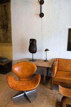 the splendid Swan Chair, in tan leather, by Arne Jacobsen.