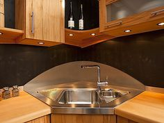 tainless steel corner kitchen sink with wooden cabinets and countertops