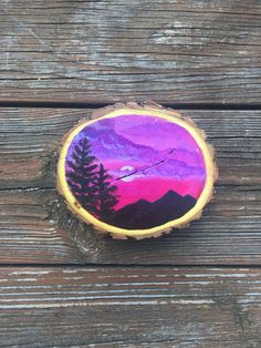 This is an acrylic painting of a beautiful mountain silhouette. The locust wood this painting is created on gives the final piece a textured and rustic finish. This adds something special to the subject matter focusing on nature and the mountains. The background of this painting is made up of vivid pinks and purples. SIZE OF WOOD: Approximately 5 x 4.5 and 1 thick Each side of the wood is sealed with two layers shellac before the painting is created to ensure the wood is protected. Each…