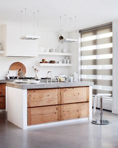 Immaculate white kitchen combined with natural materials like wood and concrete