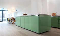 Compact yet spacious: the kitchen consisting of a cooking block and a cabinet line offers plenty of storage space for dishes and pots, without any cupboards. Wasabi is this bright green color, which gives the room freshness and the rightseasoning.  Small but effective detail: The slightly recessed base makesthe whole kitchen unit look like …