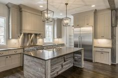 Stunning cottage kitchen features a pair of Darlana Lanterns illuminating a reclaimed barn wood island topped with gray quartz fitted with a farmhouse sink and deck mount vintage faucet atop a stained oak wood floor.