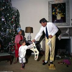 JFK hands a stocking to his son, John F. Kennedy Jr (center) while Gustavo Paredes (left) the son of his wife's assistant, looks on during the family's Christmas in Palm Beach, Florida in 1962 John Kennedy Jr., Os Kennedy, Caroline Kennedy, Jacqueline Kennedy Onassis, Orange Bowl, Martha's Vineyard, Familia Kennedy, John Junior, Jfk Jr