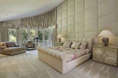 This spacious master bedroom has delicate hints of pink and an upholstered accent wall.  Find 21 stunning master bedrooms with couches or loveseats at http://www.homestratosphere.com/bedrooms-couches-loveseats/