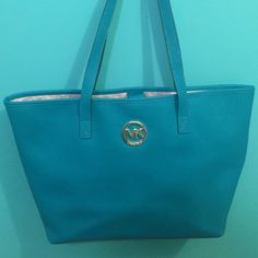 Authentic saffiano leather Michael Kors tote In good condition, one small ink marking on inside. The bag is a turquoise color. Is great for traveling or great for a lady who likes to carry a bigger bag. Willing to negotiate Michael Kors Bags Totes
