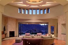 Contemporary adobe family room, great room, living room, family room, curved living room, clerestory windows, adobe interior, floor to ceiling fireplace, up lit ceiling, curvilinear living room, dramatic and neutral living room, sliding patio doors, Arizona retreat, garage door in great room