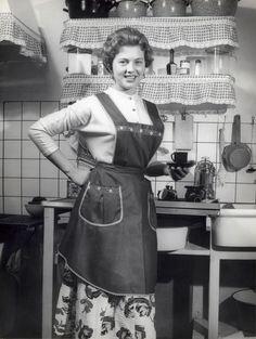 Een huisvrouw met schort aan poseert trots in haar keuken met een kopje en schotel in de hand, Nederland, jaren '50..