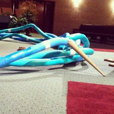Gene Holley Jr fromLife Tabernacle Church in Wichita Falls, Texas brings us this circular crown of thorns sitting on top of their congregation. They made their 9' crown of thorns out of 32 pool noodles! They bought them for $1 each at a dollar store. They inserted wire through the open cavity in the middle of the noodles and they connected the noodles together with 4' dowels and duct tape. They used a heat gun to melt the noodles to look uneven like twigs would be. Then they painted ...