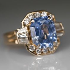 This attractive vintage sapphire ring is centered with a gorgeous cut cornered rectangular cut light blue sapphire.  This large unheated natural sapphire weighs in at 6.20 carats and is a medium light blue hue with moderately strong saturation and 11-20% windowing.  The stone is surrounded with a channel set halo of high quality baguette cut and round brilliant cut diamond accents.  This ring is handcrafted of solid 14k yellow gold and is in very good condition.