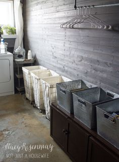 vintage industrial laundry room - sorting baskets, folding & hanging station with individual crates for each family member