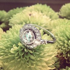 In this vintage-inspired engagement ring, a bezel-set center diamond floats above a halo of diamond accents bordered by an octagonal frame. #BrilliantEarth