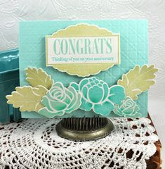 """Now, how about we chat about today's projects?  First up is a sweet anniversary card in a springy, yet soothing color scheme.  I used the Celebrations die to die cut the frame and stamped one of the coordinating frame images using spring moss ink.  Next, I stamped the """"CONGRATS"""" sentiment from Celebrations using aqua mist ink, followed by the """"Thinking of you on your anniversary"""" sentiment (also from Celebrations) using hawaiian shores ink.  Behind the frame, the cane print impression plate…"""