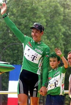 Erik Zabel, joined by son Rick, receives his fifth green jersey at the 2000 Tour de France. Rick is now taking after his father and is a successful Junior racer.