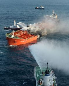 Fire on tanker: Firefighters spray water from their vessels onto a chemical tanker off the coast of Busan Sunday after the tanker caught fir...