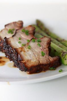 Sanft gegrillter Schweinebauch, der vorher mit einem Rub aus vielen Gewürzen mariniert und gegen Ende der Grillzeit glasiert wurde. Dazu grüner Spargel.