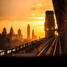 View of Philadelphia Skyline as seen from a train car on the Ben Franklin Bridge The sun is setting behind the tower in the right of the frame showing just enough of the dirty window and the track...