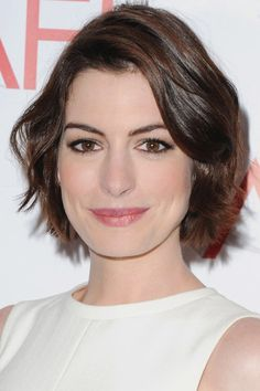 Anne Hathaway adds soft waves and a deep part to create a feminine version of her grown out pixie cut.