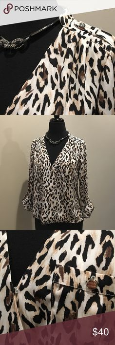 """White House Black Market Leopard Top Only worn twice!! This fabulous top features: a high/low design, sleeves that can be cuffed or worn down, a snap closure in the front for an easy on, and it's made of 97% polyester and 3% spandex. It measures approx. 20-1/2"""" from the shoulder to the hem in the front and approx. 26"""" from the bottom of the collar to the center of the hem in the back. Washes up great! It would be great with a pair of black skinny pants and knee high boots!! This top is a…"""