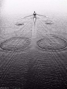 Rower in the water with raindrops