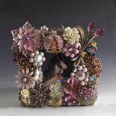 This sweet handcrafted frame is composed of vintage costume jewelry in shades of pink with gold and pearly white. Amid carved roses, enamel on metal flowers, pearls, rhinestones, and more is a wonderful pink jeweled ladybug. The frame is gold patina on wood with a sturdy easel back.