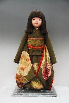 An Ichimatsu doll in a dark olive green silk kimono and obi.