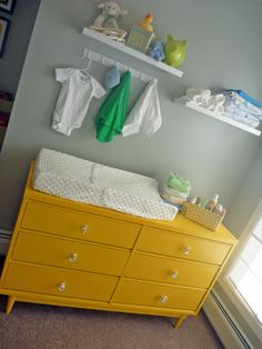 Love the idea of the tiny coat rack above the dresser. Yellow and grey nursery
