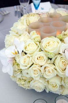 Tea candles are nestled into an arrangement of white roses and orchids.