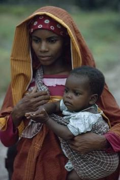 Photographic Print: A young woman of Arab descent holds her young child. by Volkmar K. Wentzel : 24x16in