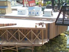 Close up detail of ramp construction with the three out-buildings for the planned Urban Grain Elevator on the Taltree Railway Garden Urban Vignette. These models were built by David Besterman and Ron Whittingham. The right hand side of this photo is the end of a single leaf Bascule Bridge (which is a movable span bridge which rotates on a trunnion). This type of bridge can still be found today in many urban areas where trains have to cross rivers including Kinzie St in Chicago. Elevator, Water Garden, Rivers, Vignettes, Trains, Buildings, Bridge, Chicago, David