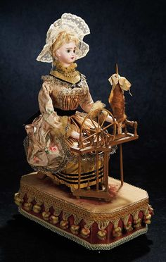"""1890, French Bisque Musical Automaton, 20"""", When wound,music plays and the doll turns head from side to side,while spinning the wheel with her right hand,and turning the flax holder with her left."""