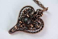 Heart of All - This handcrafted wire wrapped copper pendant is delicately woven in the form of a unified heart. Adorned with Larvikite stones along with copper beads the pendant is suspended from a cooper chain with lobster claw clasp. Larvikite - is a protective and grounding stone. It is cleansing to the subtle bodies and facilitates a strong connection with the energies of Earth, helping to connect with the spirits of Nature.