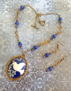 Dove Necklace .. made with Polymer Clay .. A Brass B'sue Bezel .. Handmade Brass Connectors .. Blue and Purple Glass Beads and Brass Chain .. matching earrings to complete this set .. Designed by .. Jann Tague .. Clever Designs .. https://www.facebook.com/#!/JewelsByJann