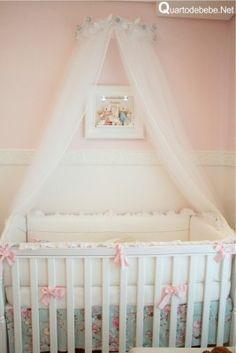 enxoval de berço com flores, lacinhos rosa e dossel floral branco com voal caindo sobre o berço super delicado. Detalhe do quarto de bebê com parede rosa.