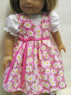 This is a sweet little outfit for your 18 American Girl doll. The fabric has bright white daisys scattered on a bright pink background. The jumper bodice is fully lined and fastens in back with velcro. It can be worn without the blouse as a sundress. Her crispy white blouse has