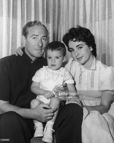 1957: A family portrait of British-born actress Elizabeth Taylor, wearing a high-necked dress, sitting with arm around husband, British actor Michael Wilding (1912 - 1979), who holds their son, either Christopher or Michael Jr., in his lap.